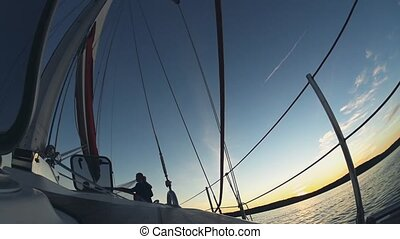 Yacht sailing on the wind on sunset. Beautiful newlywed couple, bride and groom spending time in open water.