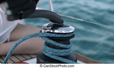 Yacht winch operation girl is working - Yacht winch...