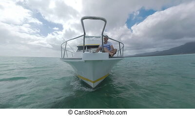 Yacht with man on front deck sailing to Mauritius Island