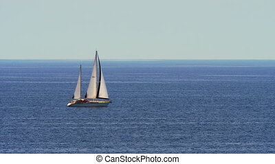 Yacht with sails in quiet blue sea - Lonely yacht sailing in...