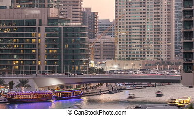 Yachts and boats with tourists staying near shoping mall and passing under a bridge in Dubai Marina district day to night timelapse.