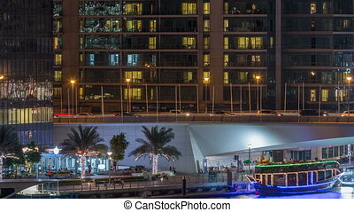 Yachts and boats with tourists staying near shoping mall and passing under a bridge in Dubai Marina district night timelapse.