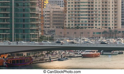 Yachts and boats with tourists staying near shoping mall and passing under a bridge in Dubai Marina district timelapse.