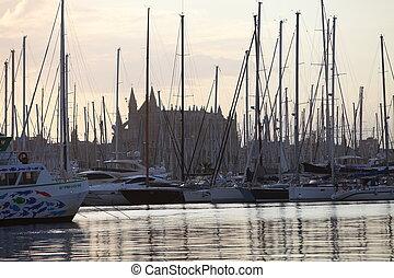 Yachts moored in a marina below a church