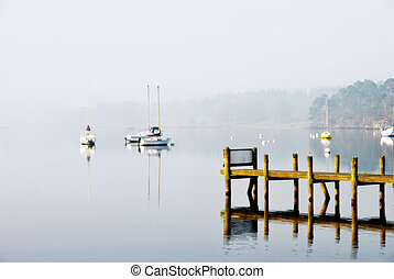 Yachts moored on a misty lake - Pleasure yachts moored to ...
