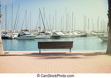 Yachts near the shore in the port, the city of Alicante