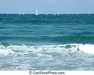 Yachts on sea open space. Waves by the sea. White sails in...