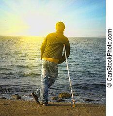 Yang man hiking on crutches