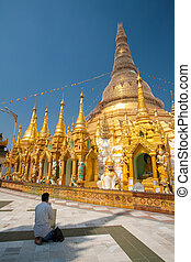 YANGON, MYANMAR - JAN 22: Unidentified Buddhism Sitting with hands clasped respected to Shwedagon Pagoda Dec 6, 2014 in Yangon. Buddhism is predominantly of the Theravada tradition, practised by 89% of the population.
