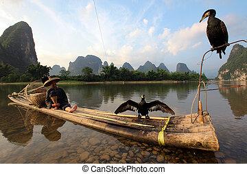 YANGSHUO - JUNE 18: Chinese Chinese man fishing with ...