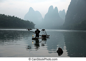 YANGSHUO - JUNE 19: Chinese man fishing with cormorants...