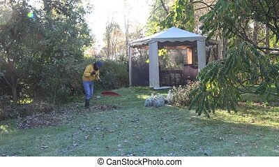 Yard keeper in yellow sweater rake leaves in garden at cold autumn morning 4K