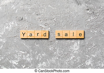 Yard sale word written on wood block. Yard sale text on cement table for your desing, Top view concept