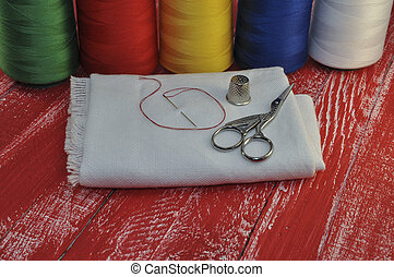 Yarns, fabric, scissors, a thimble for home crafts