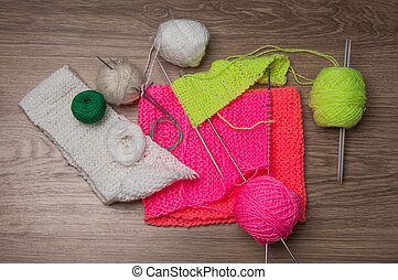 yarns, wool, knitting needles on dark background