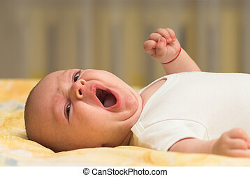 Yawn - Little baby is yawning in a bed