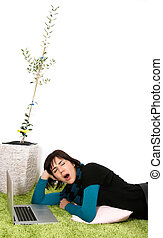 yawn - Woman with laptop yawningwith olive tree in...