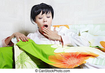 Yawning lady on the bed covered by colorful blanket