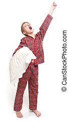 Yawning boy -  Yawning boy in pyjamas holding a pillow