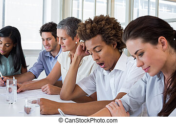 Yawning casual businessman in a meeting