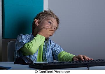 Yawning kid using computer