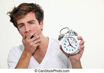 Yawning man holding alarm clock