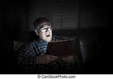 Yawning man reading tablet at night