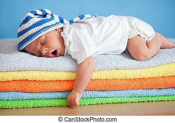 Yawning sleeping baby on colorful towels stack