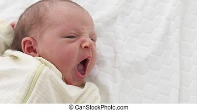 Yawning tiny newborn baby - From above of newborn baby in...