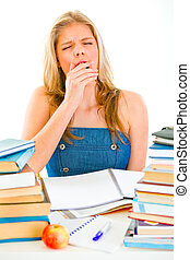 Yawning tired teen girl sitting at table with piles of books...