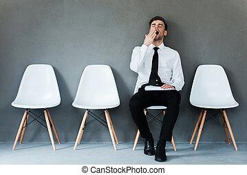 yawning, vasthouden, zittende , moe, jonge, tegen, grijze , terwijl, papier, achtergrond, zakenman, waiting., stoel