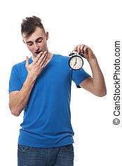 Yawning young man holding alarm clock