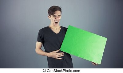 Yawning Young man in black shirt holding green key sheet poster gray background