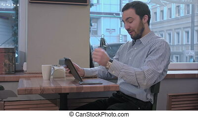 yawns young man using tablet computer in cafe and loking in...