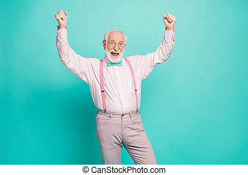 Yeah. Photo of funny attractive crazy excited grandpa raise fists up celebrating money income wear specs pink shirt suspenders bow tie pants isolated teal color background