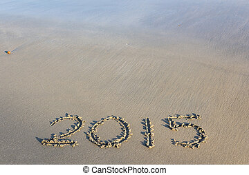 Year 2015 number written on sandy beach.