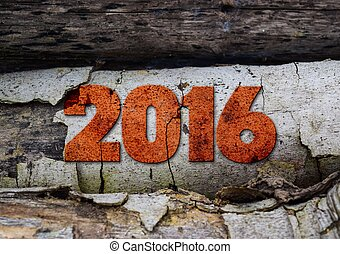 year 2016 written with vintage letterpress printing blocks on rustic wood background