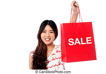 Year end sale started! - Young trendy girl holding up...
