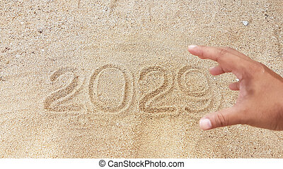 Year handwriting on sand with foreground of blurry reach out hand