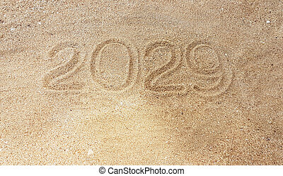 Year handwriting on sand with reach out of survivor hand