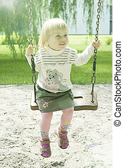 Year-old girl riding in the park on a swing
