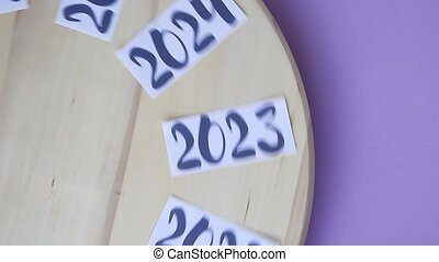Years from 2014 to 2024 rotating on wooden board and stopped...