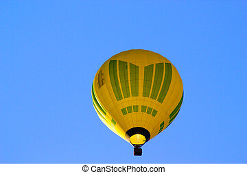 Yellow air balloon on the blue sky background. View from bottom