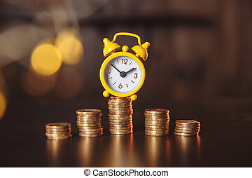 Yellow alarm clock and stack of coins with financial concept
