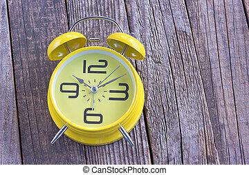 Yellow alarm clock on wooden background