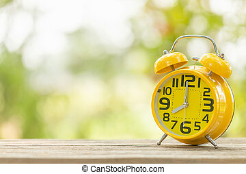 Yellow alarm clock on wooden table with green outdoor nature blur background