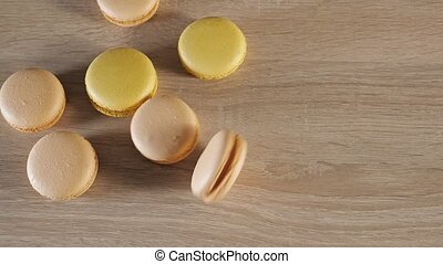 Yellow and beige macaroons on wood background, one cookie...