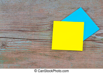 yellow and blue sticky note with empty space for a text  on wooden background