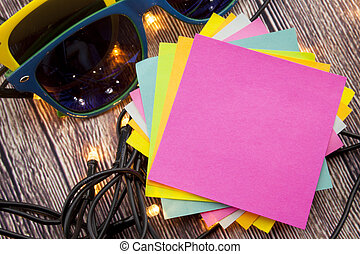 Yellow and blue sticky note with empty space for a text on wooden background.