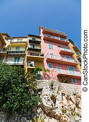 Yellow and Pink Condos Over Stone Wall